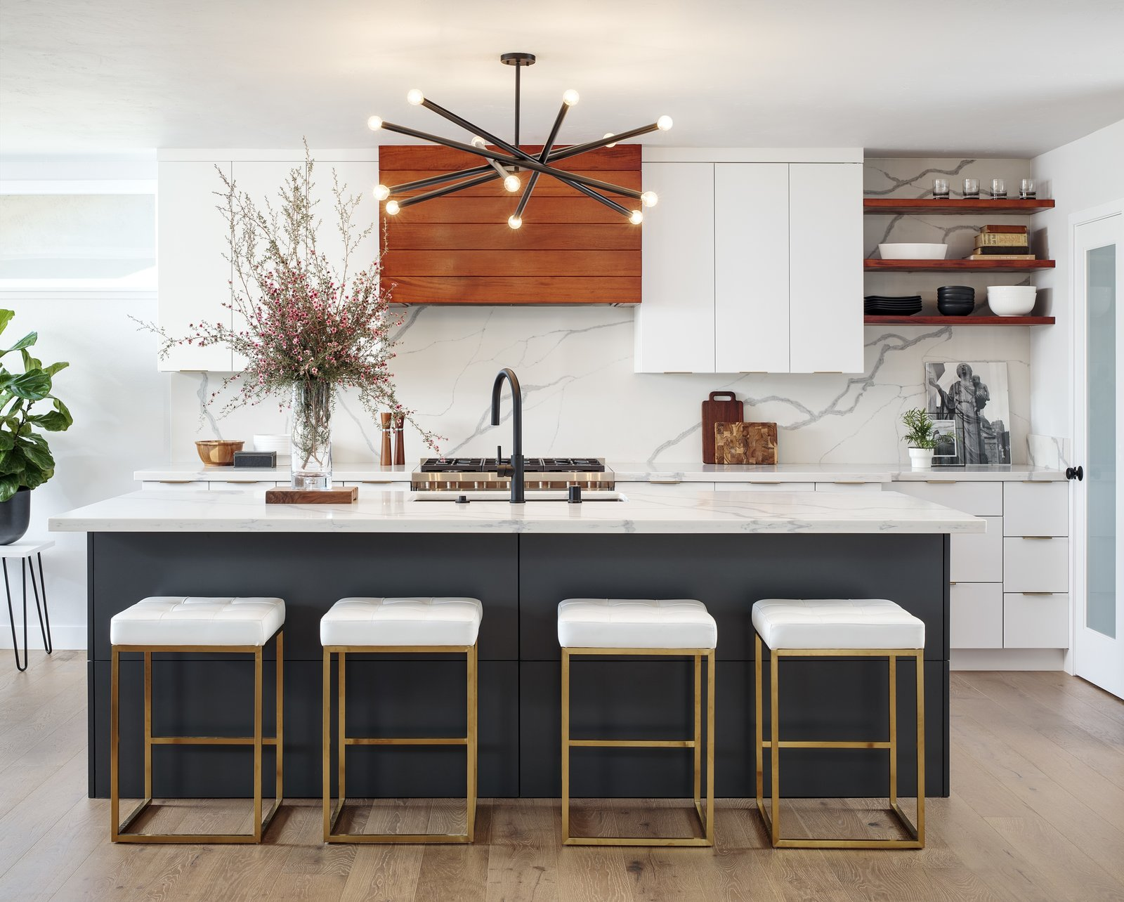 White cabinetry and white marble match against wooden accents in a Contemporary kitchen