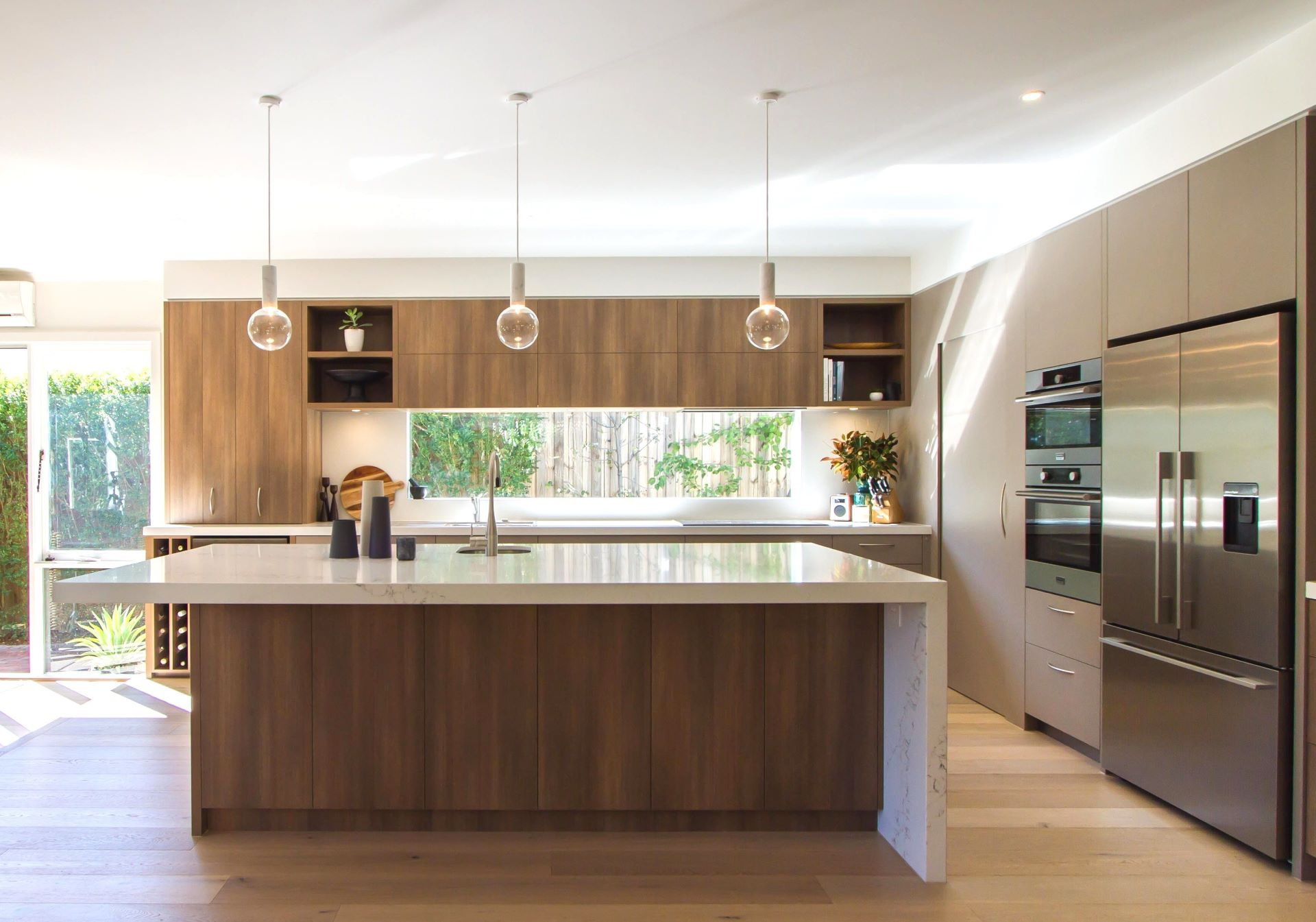 Mix of modern glass light, wooden flooring, wood cabinetry, and metallic kitchen appliances in Contemporary kitchen