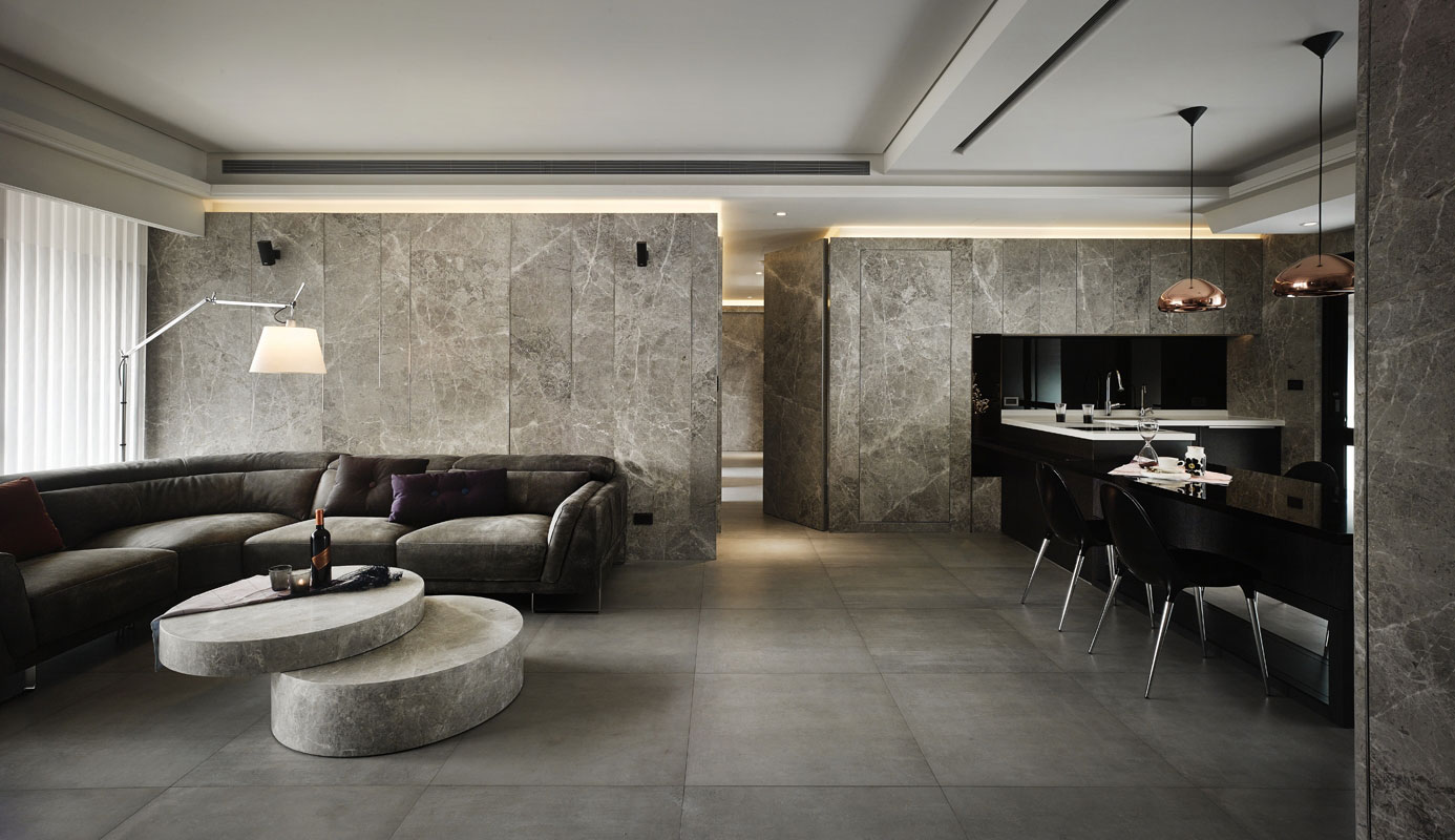 Natural granite wall and gray fabric sofa in a Contemporary-Industrial interior