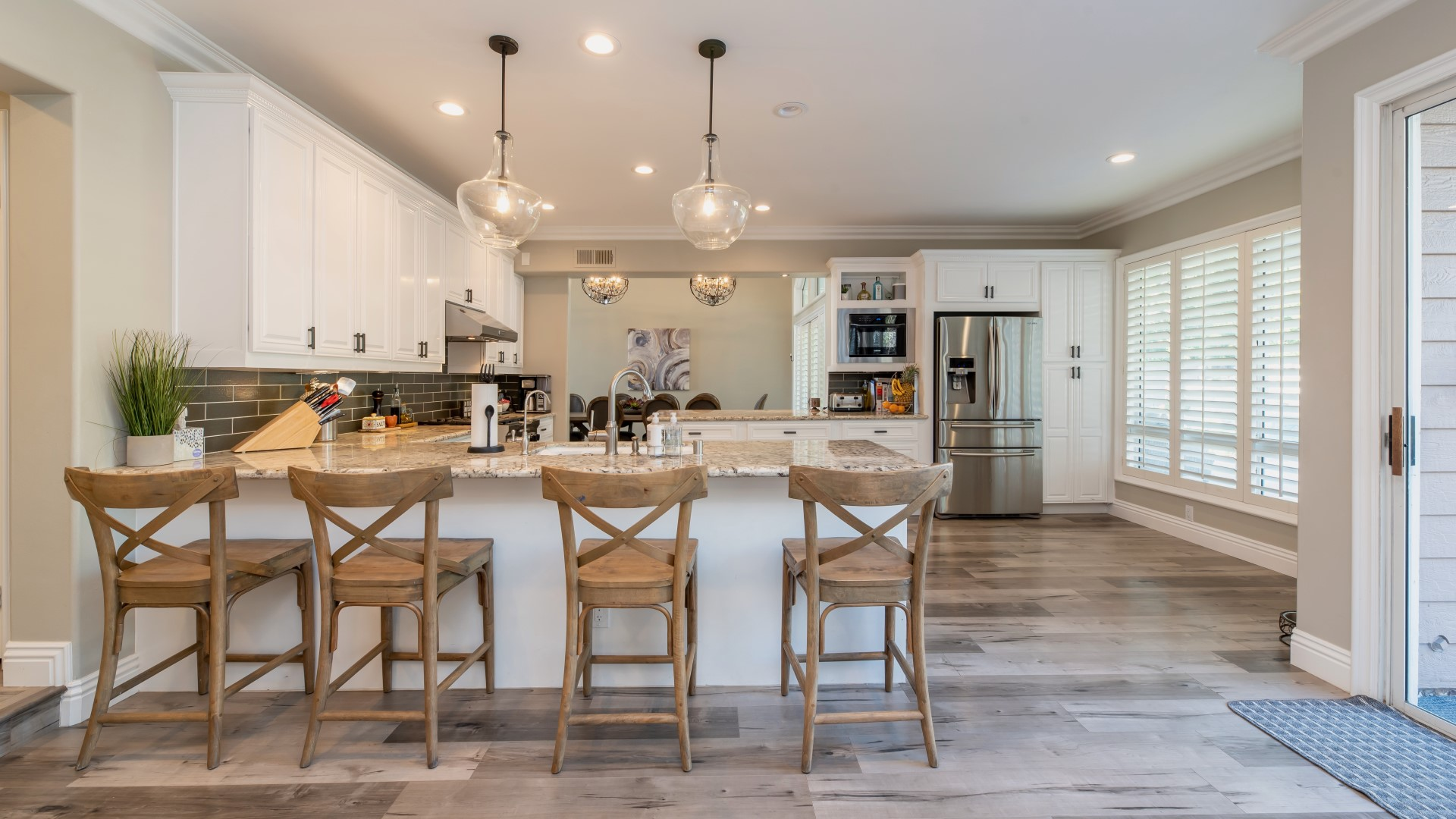 Open concept kitchen with wooden chairs lining bar countertop partition