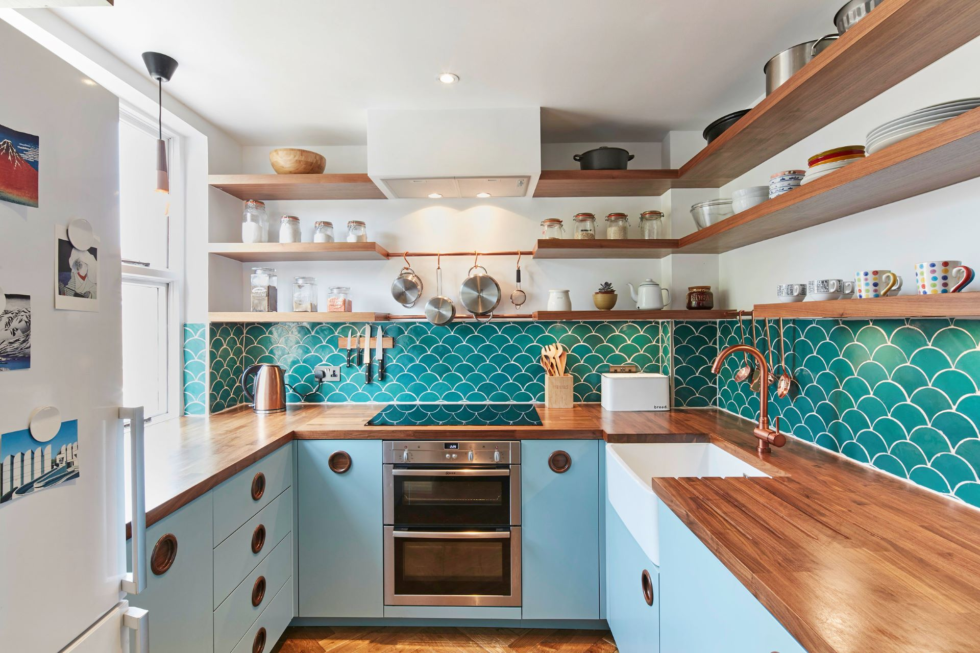Blue themed MCM kitchen with wooden countertop and shelves stocked with dinnerware