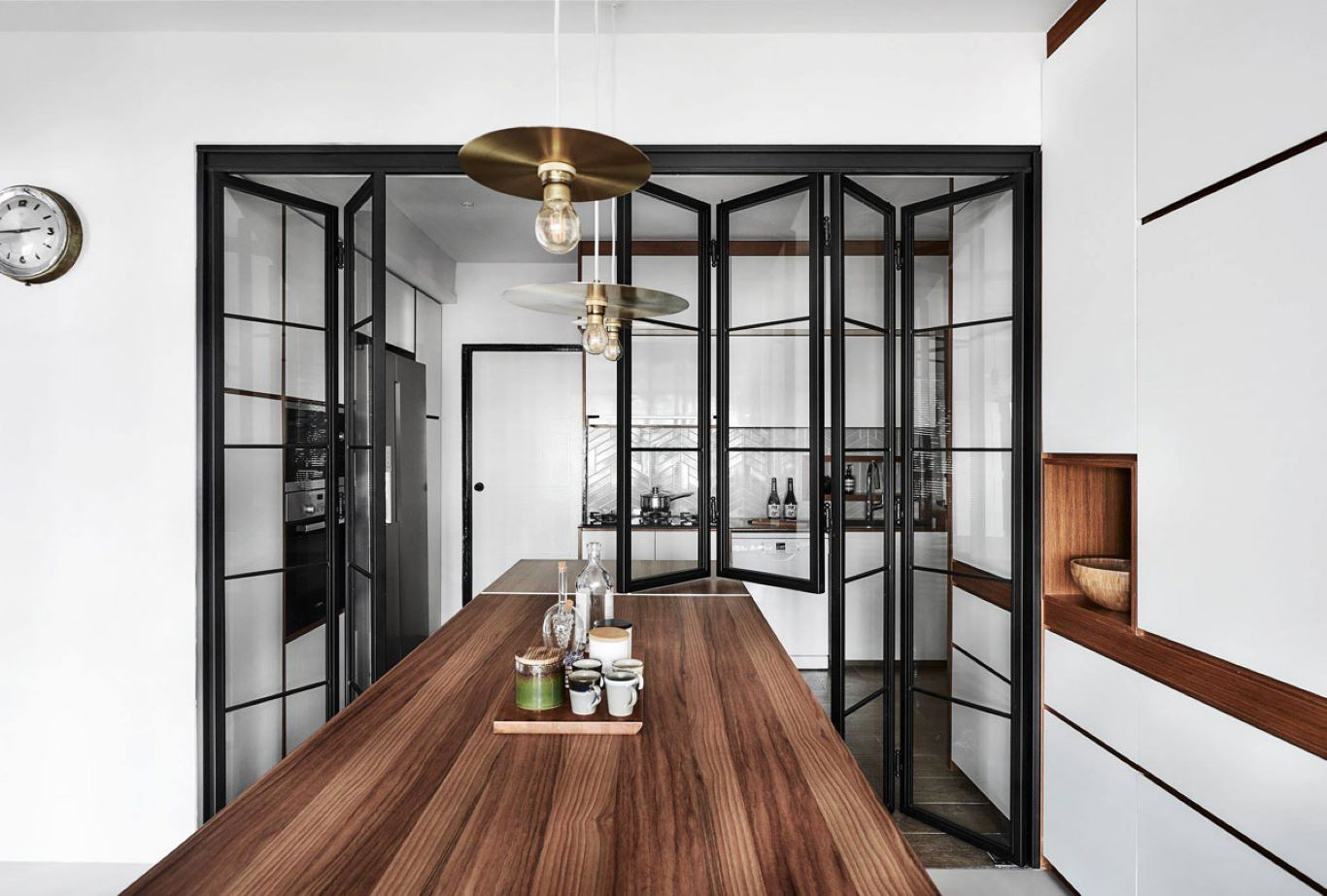 Open concept HDB with kitchen island linked to dining table beside living room and glass sliding doors partitioning bedroom