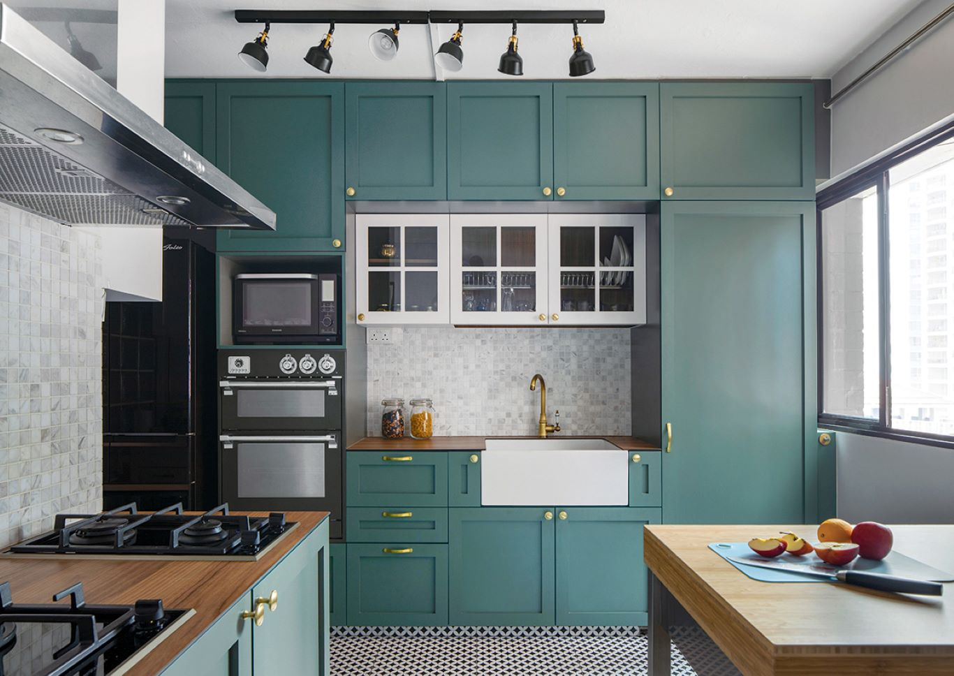 Kitchen cabinets in dark teal paired with geometric patterned flooring and wooden countertops