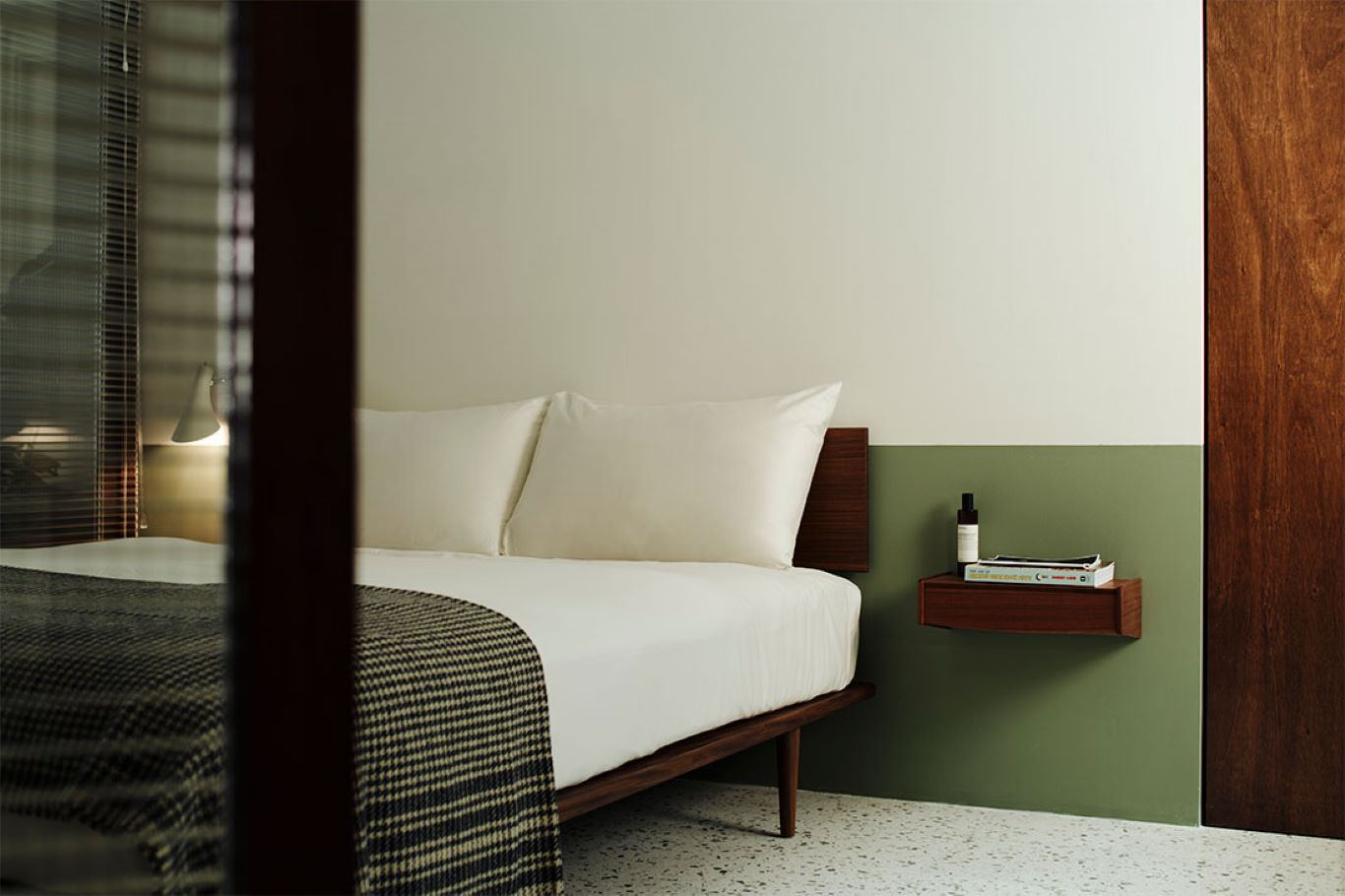 Bed frame on tapered legs atop marble flooring with simple wooden furnishings