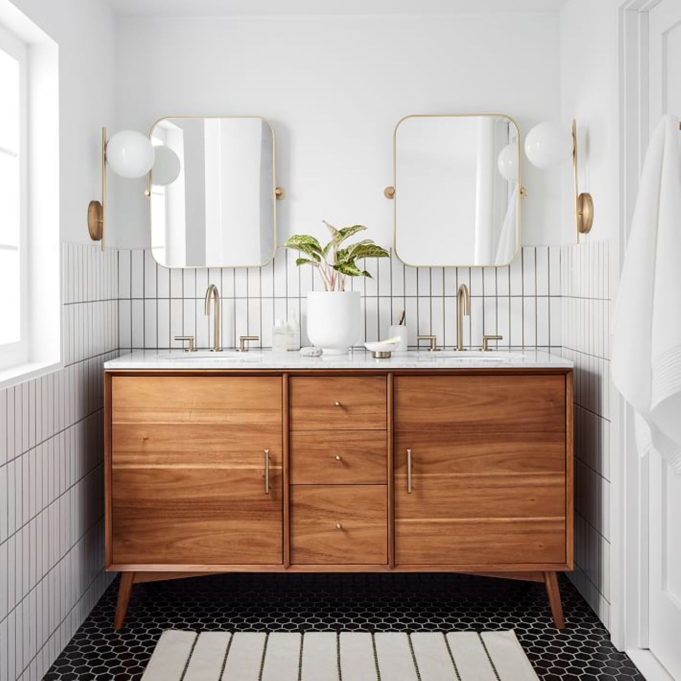 White bathroom matched with wood finishes and a brick walled shower