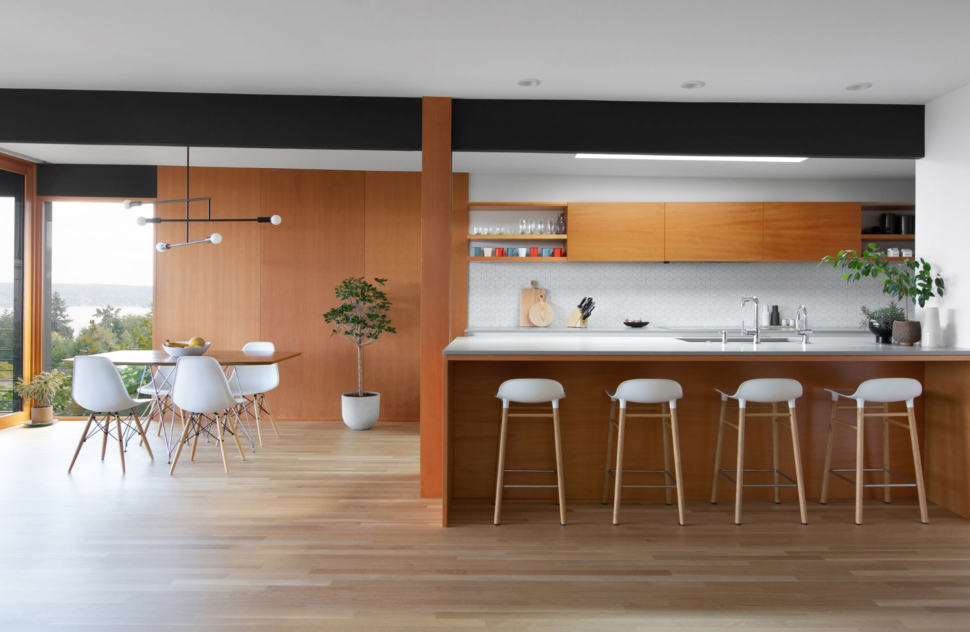 Open kitchen and dining area in darker shades of wood with white chairs and stools matched with metal lights
