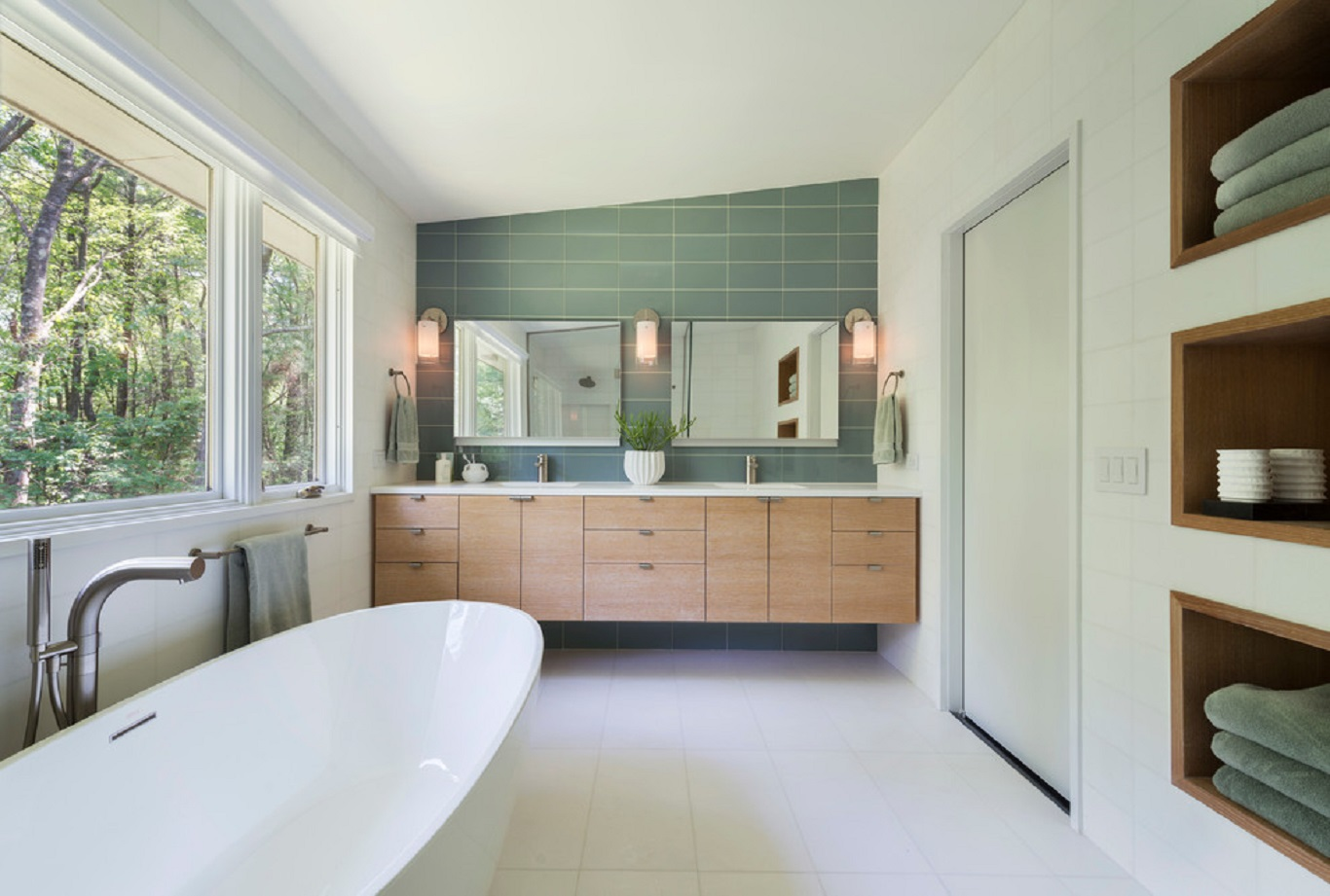 Standalone bathtub in whitewashed bathroom matched with wooden cabinets and various teal elements