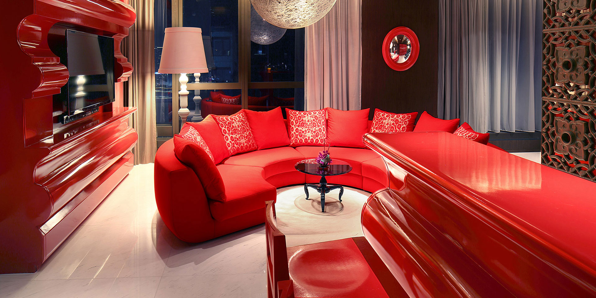 Red sofa with red cushions, red bar top with red high chairs, and red TV console in an Oriental Chinese living room