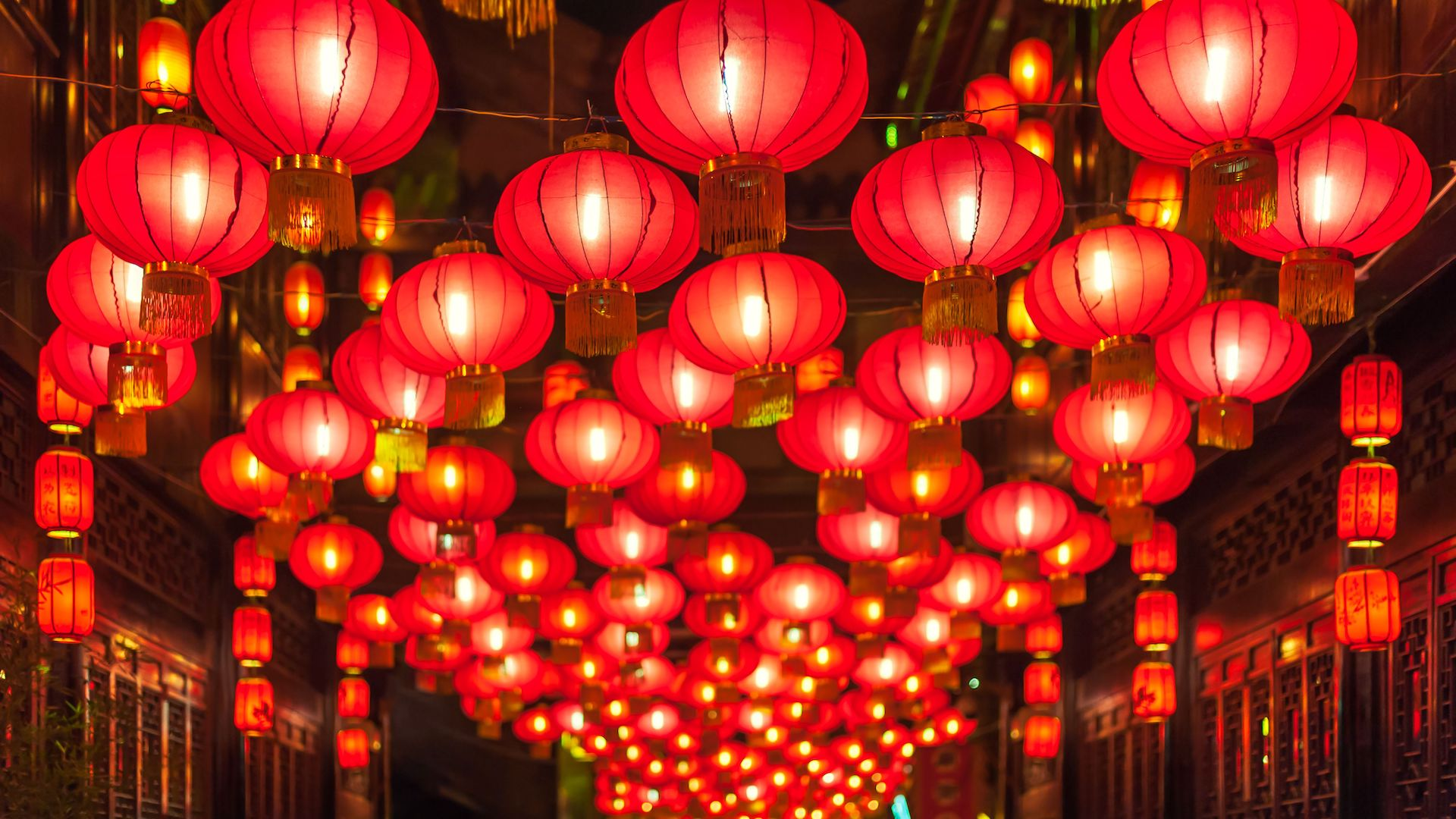 Many red traditional Chinese lanterns hanging above the middle of a small Chinese town walkway