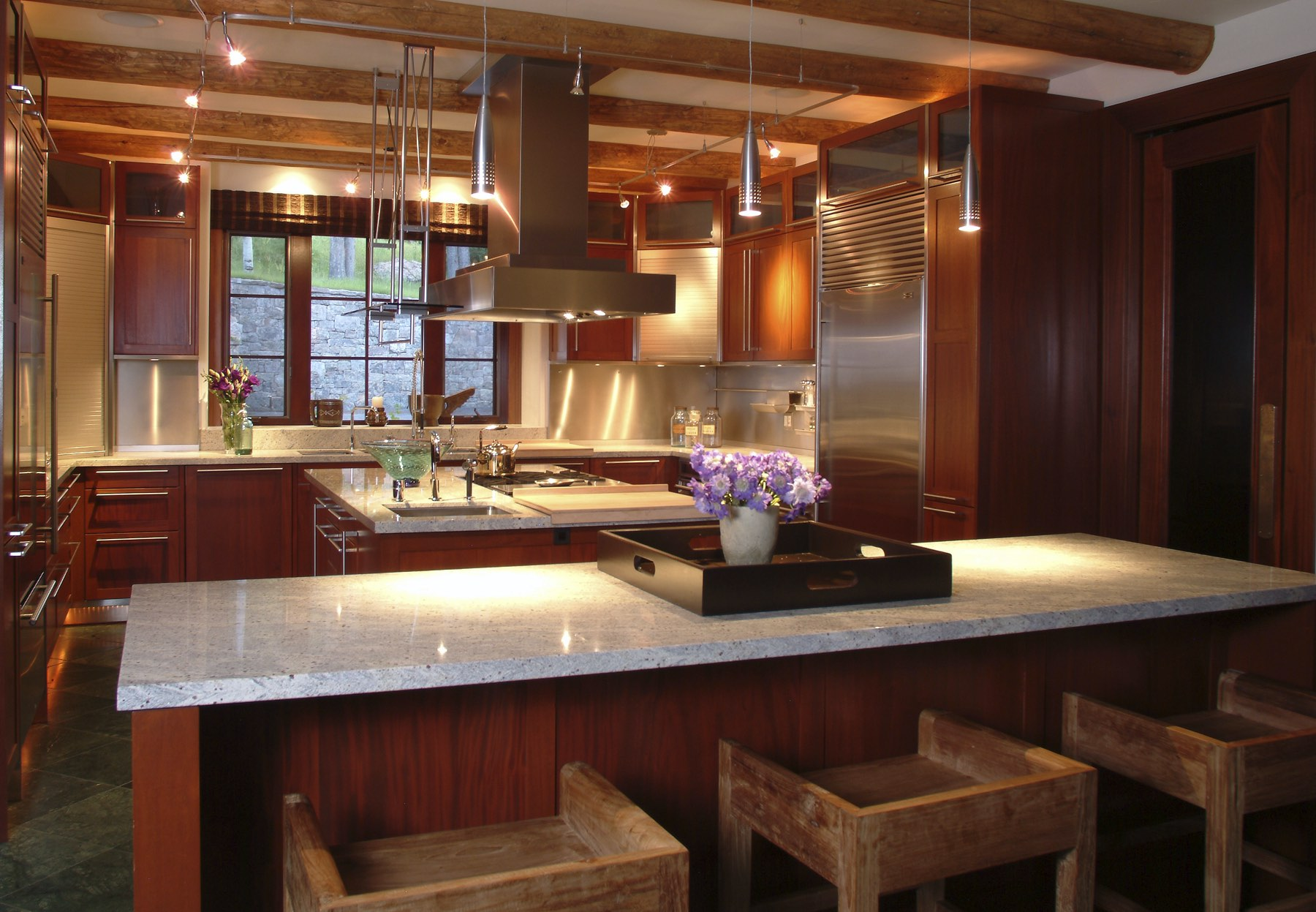 Modern kitchen with red cabinets, marble countertops, and modern appliances