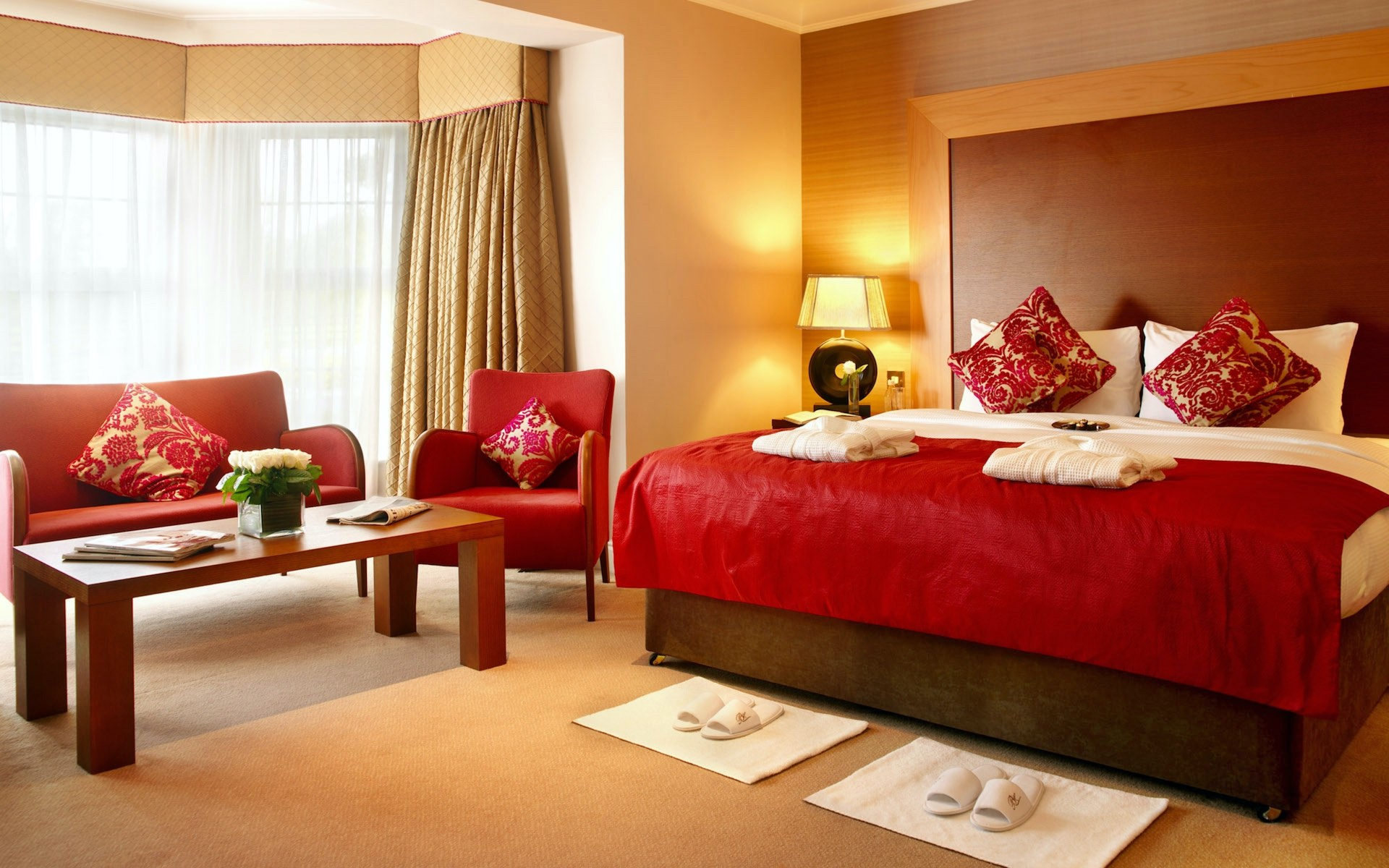Red textiles for sofa and bed cover with red and gold cushions in a modern bedroom