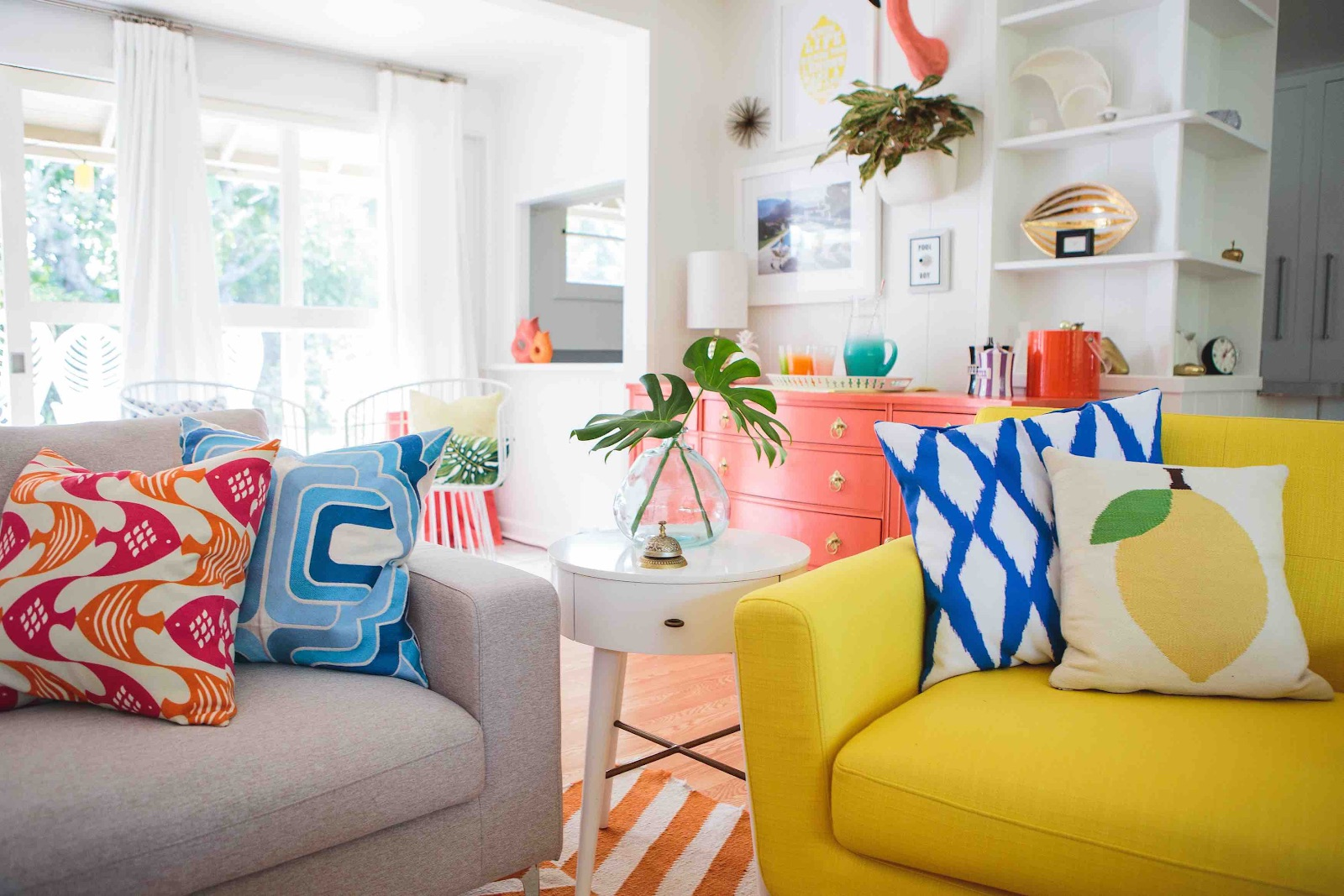Colorful cushion covers and soft throws on sofa promotes the Retro vibe in the space