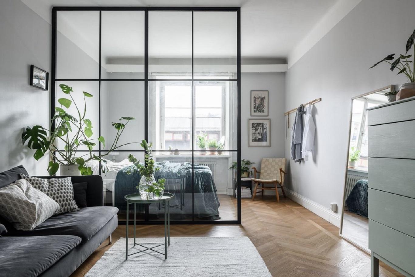 Dove gray walls, herringbone wood flooring, and tapered legged furniture speaks of cool Nordic styling