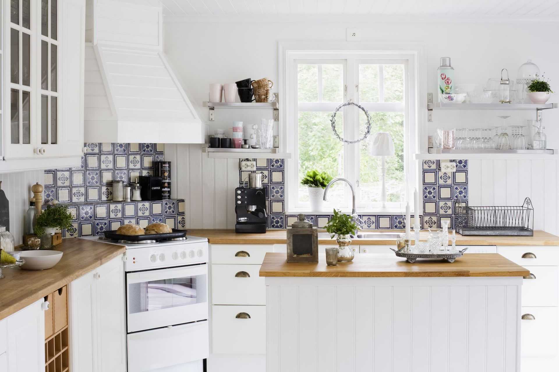 Traditional Spanish backsplash tiles give the Scandinavian kitchen top a textured effect