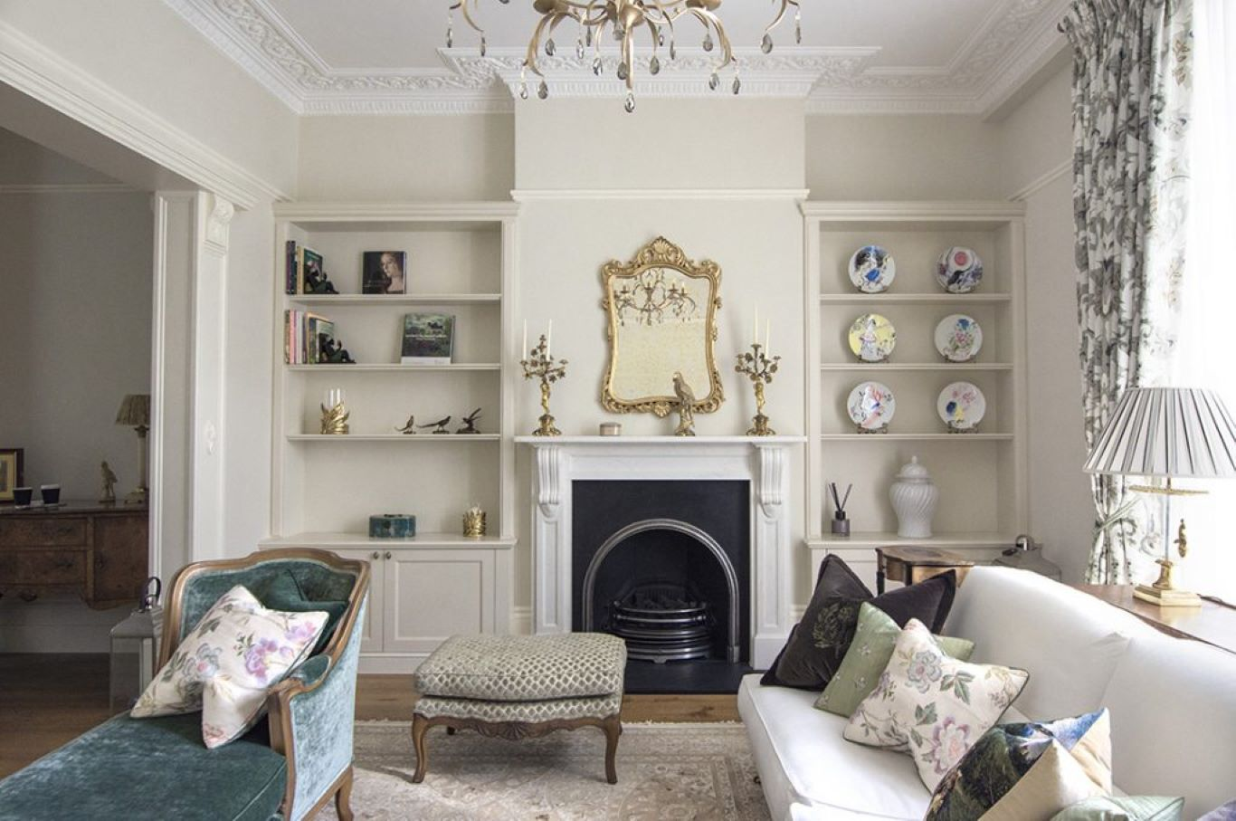 Victorian living room with chaise lounge, floral cushions  and ornately-carved mirror on wall.
