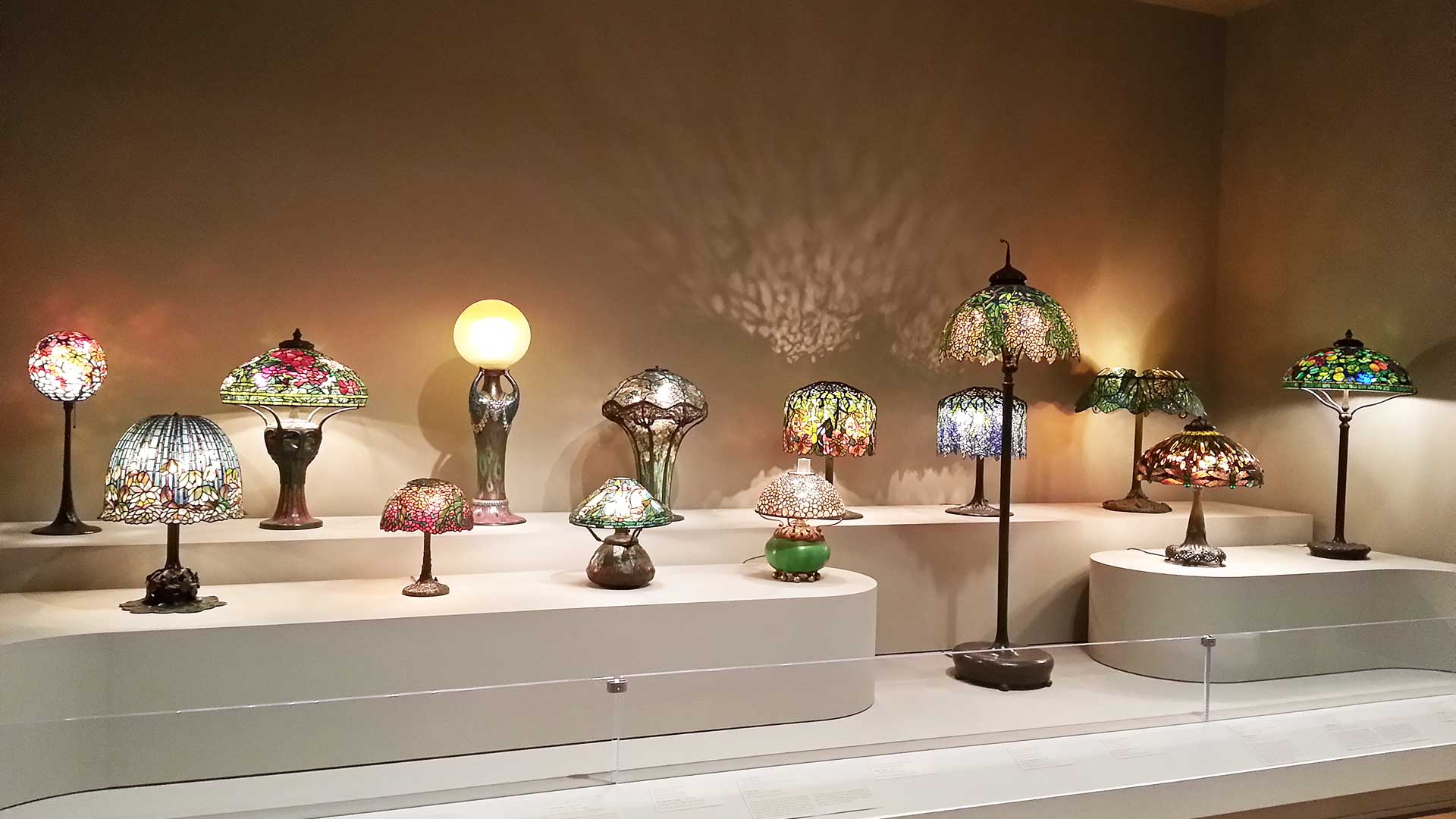 A range of Tiffany lamps in small and large sizes having different colored stained glass patterns.