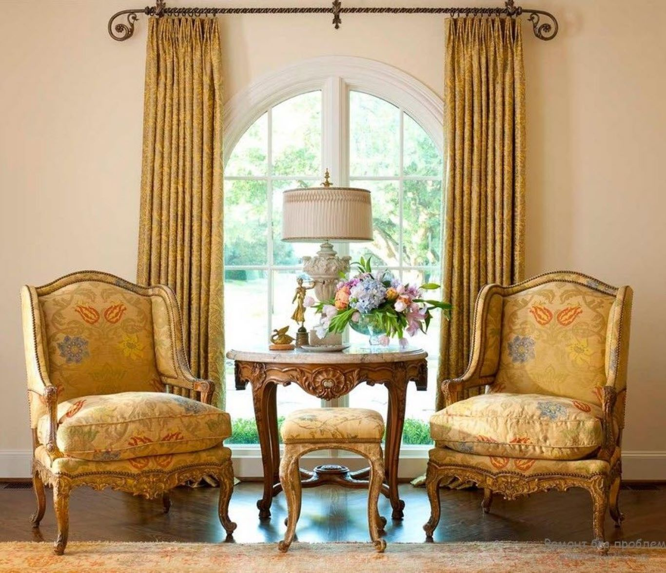 Intricate-design floor-to-ceiling curtains and two matching-toned ornate wooden chairs in a Victorian style lounge.