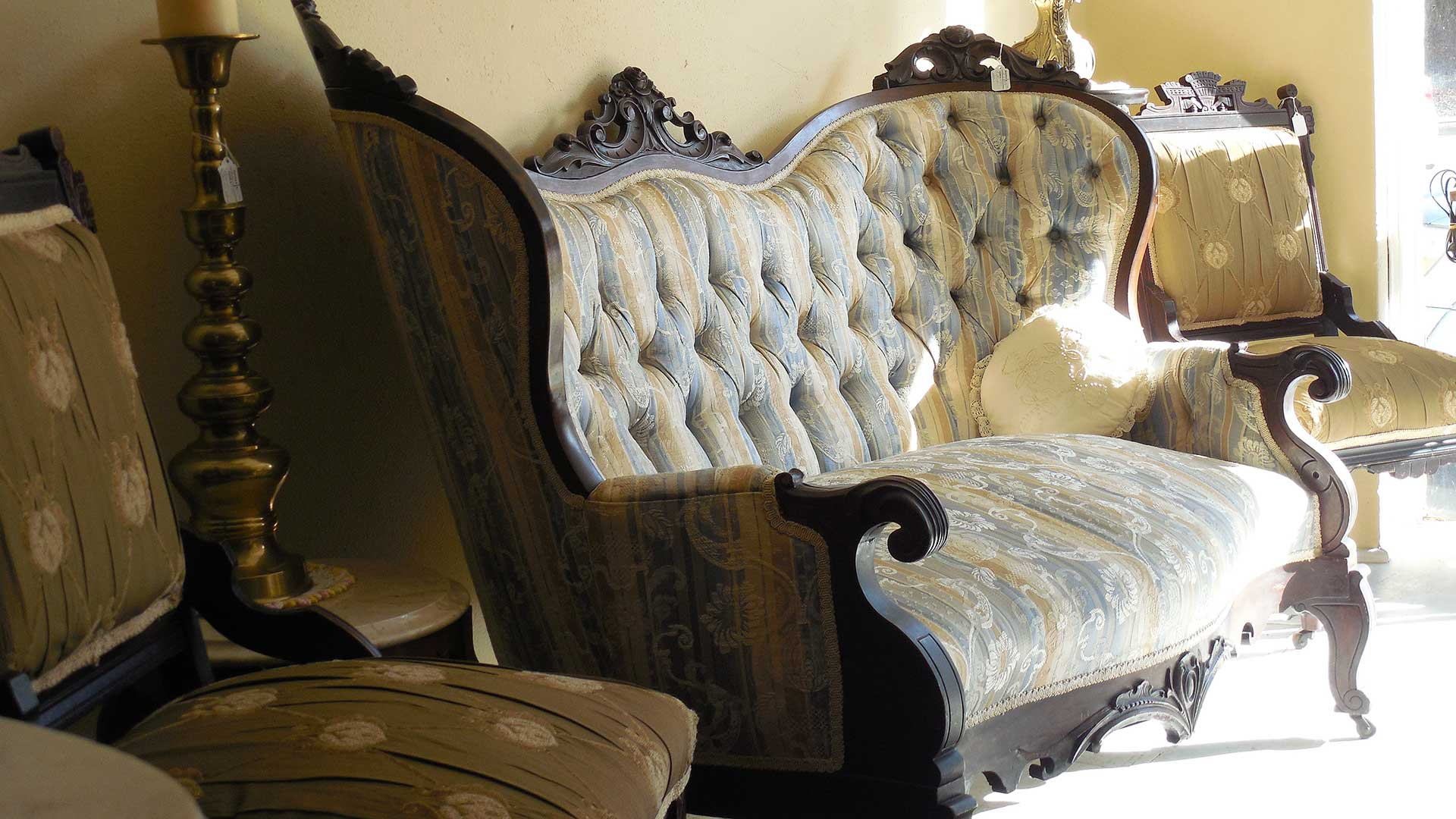 Ornately-carved wooden 2-seater sofa characteristic of the Victorian era.