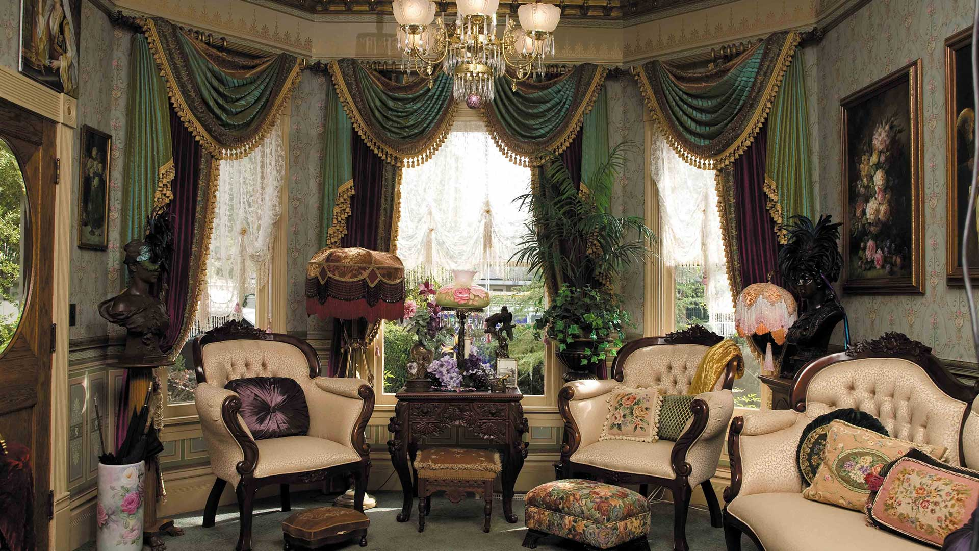 Aristocratic-style living room portraying Victorian decor, floral wallpaper, ornate furniture, and a chandelier.