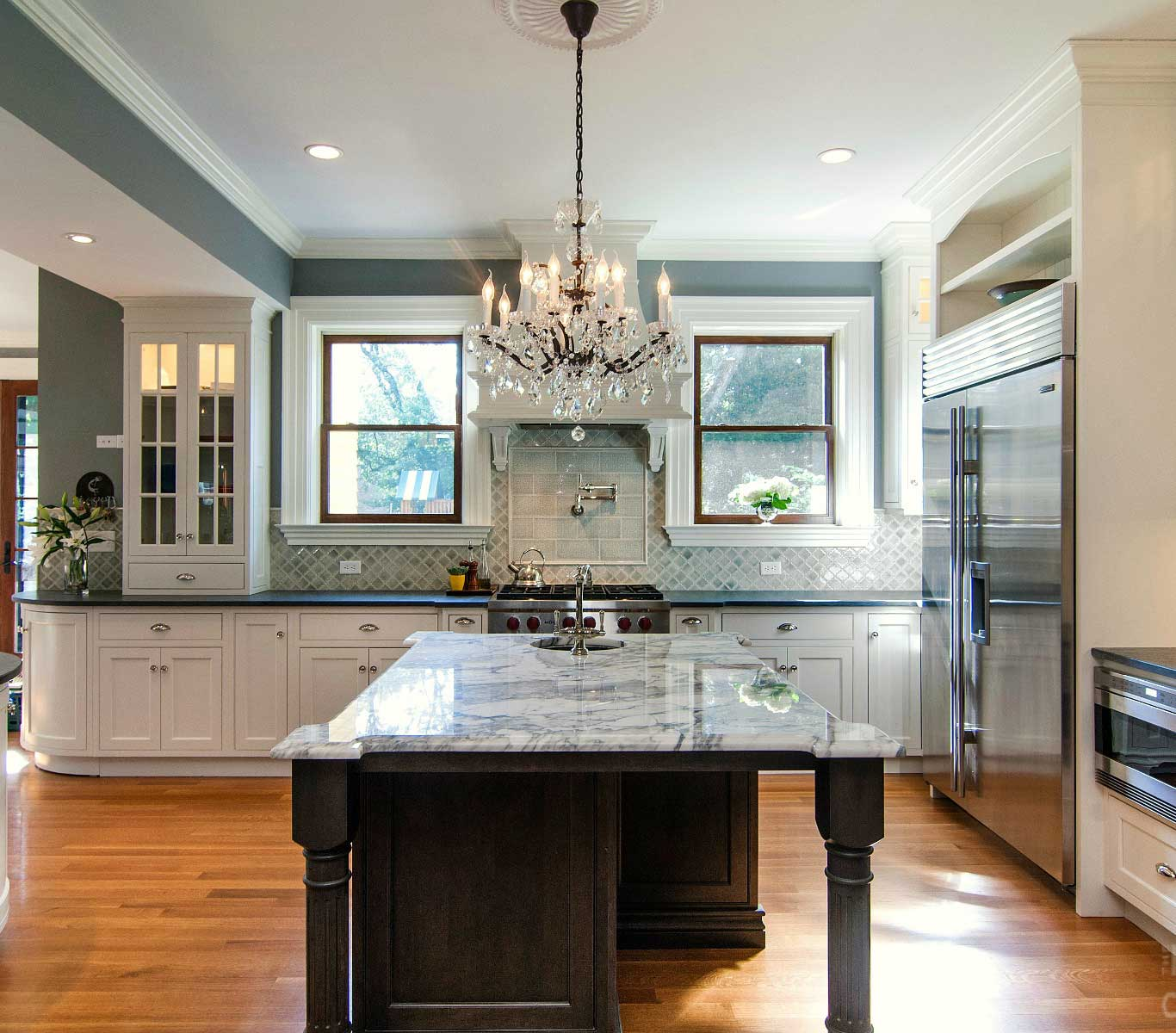 Kitchen with polished wooden flooring, center marble-top island with over-hanging crystal pendant light.