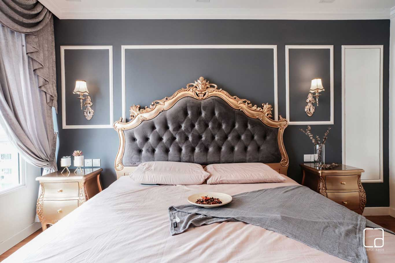 Large master bed with ornate quilted headboard against a backdrop of grey-toned walls.