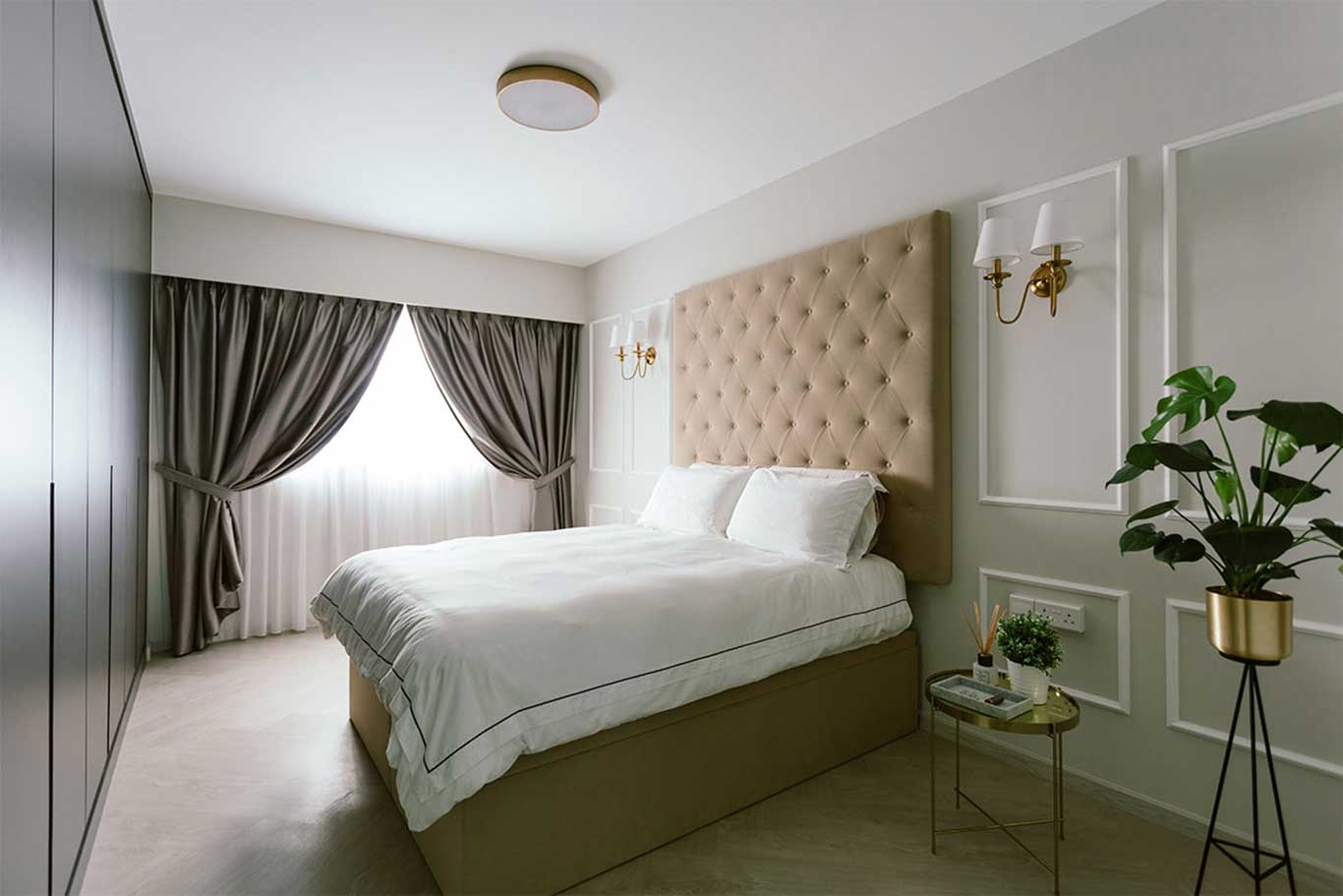 Modern Victorian bedroom with lightly- quilted headboard and sconce wall lights.