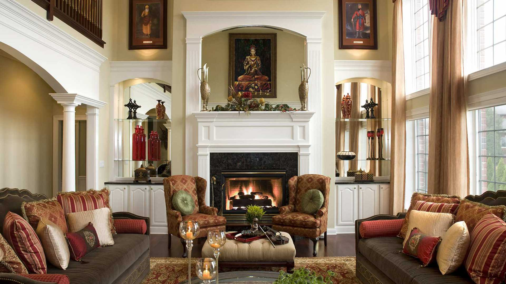 Victorian house sitting room with fabric furniture and  fireplace in the center.