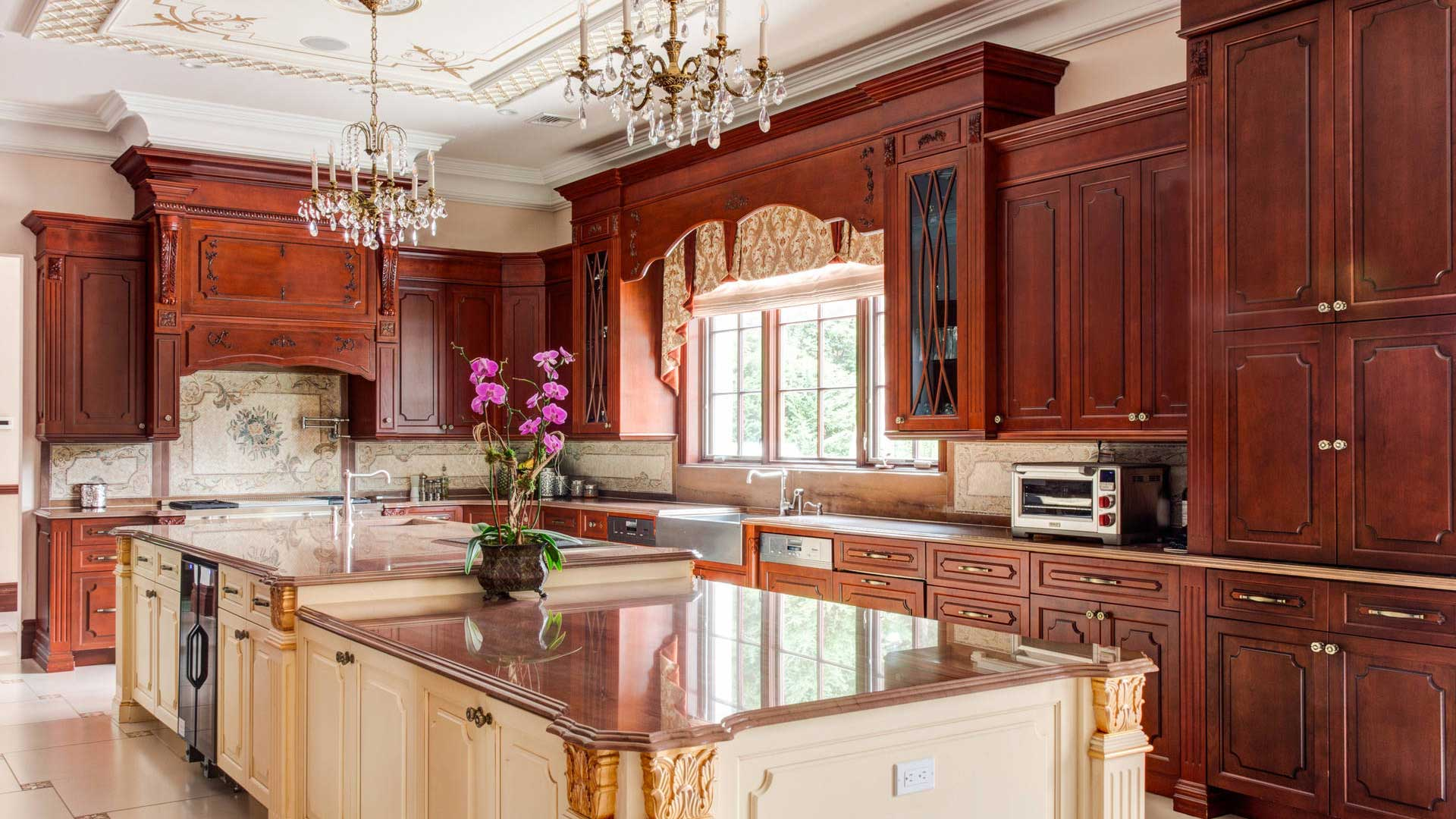 Open concept Victorian design kitchen with ornately-carved wooden center island.