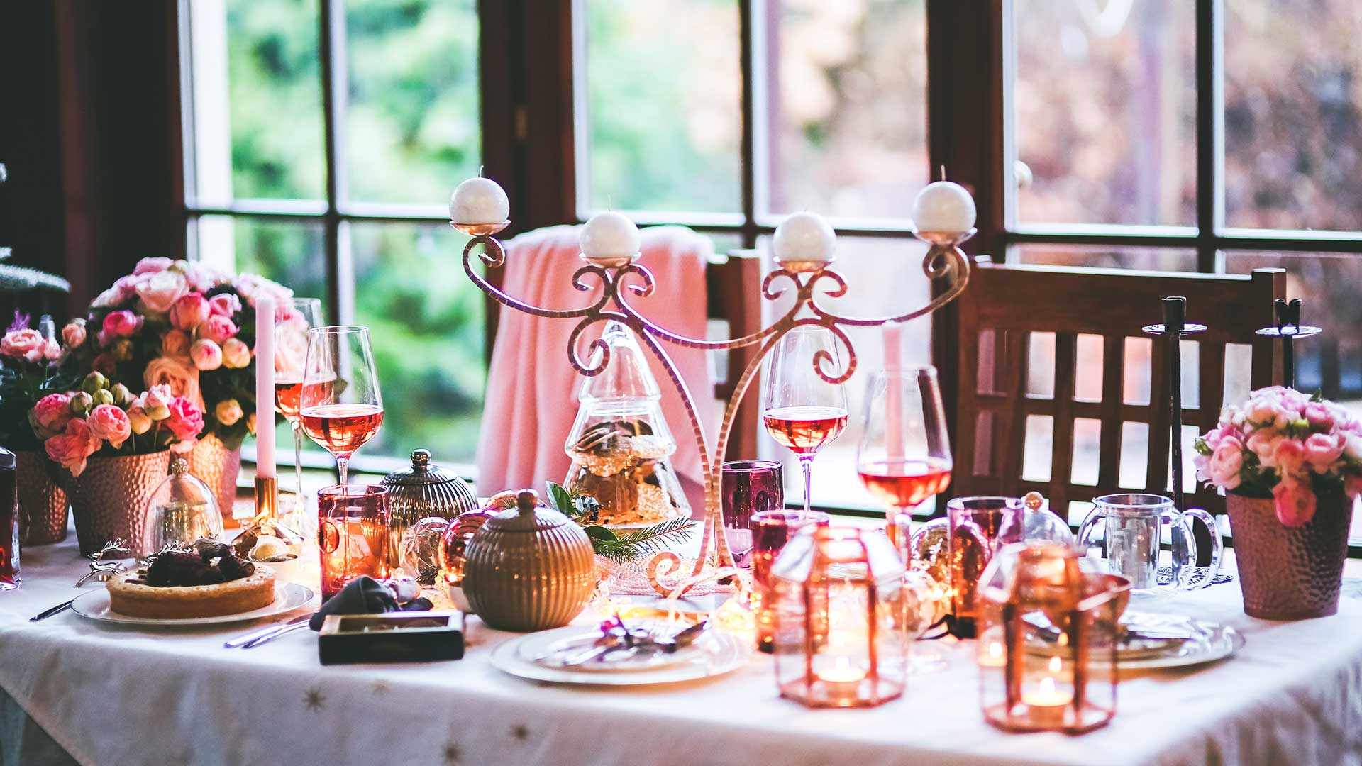 Table setting with wine glasses, mini lanterns and flower pots.
